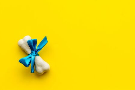 Small present for dogs. Chewing bones with bow on yellow background top view. Фото со стока - 131411327