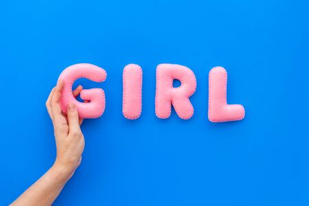 Girl word as decoration for baby shower on blue background top view.