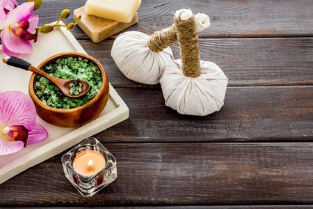 Massage thai herbal balls near spa accessories and orchids on dark wooden background.