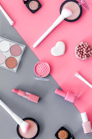 Makeup background with rounge, powder and tools on pink and grey table top view.