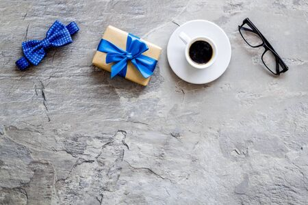 Greeting card for mens birthday. Present box, bow tie and coffee on grey background top view.