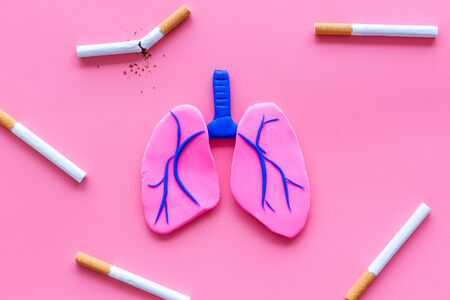 Harm of smoking and cancer. Lungs and cigaretts on pink background top view. Stock Photo