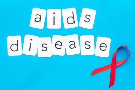 AIDS disease text near red ribbon on blue background top view Reklamní fotografie