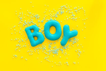 Boy word as decoration for baby shower on yellow background top view.