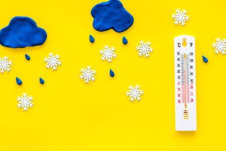 Es concepto nevando. Nieve y termómetro en la vista superior de fondo amarillo.