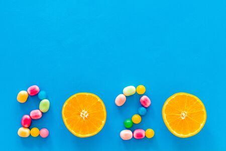 Sweet New Year design. 2020 laid out with candy and oranges on blue background top view copy space