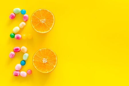 Sweet New Year design. 2020 laid out with candy and oranges on yellow background top view space for text