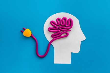 Brain charging and mental rest. Plug and cable leads to plastiline meanders on blue background top view.
