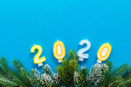 2020 New Year design. Date laid out by candles near fir branches on blue background top view copy space 写真素材