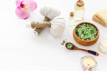 Massage thai herbal balls near spa accessories and orchids on white background copy space