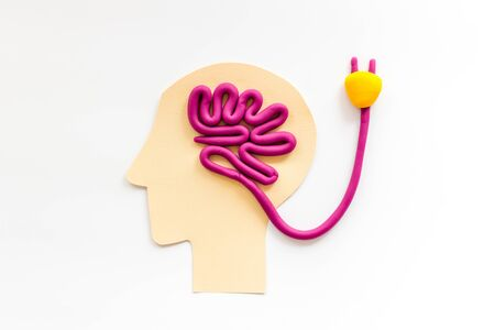 Brain charging and mental rest. Plug and cable leads to plastiline meanders on white background top view Stock Photo