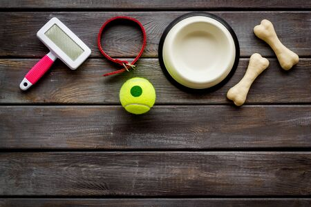Pets accessories like bones, collar and bowl on dark wooden background top view flat lay copy space