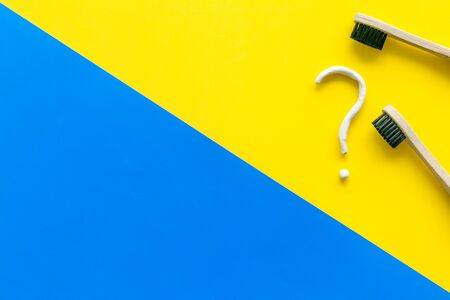 Dental problems concept. Question mark drawn with toothpaste near toothbrush on yellow and blue background top view.