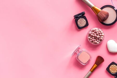 Makeup concept. Frame with decorative cosmetics and brushes on pink background top view copy space