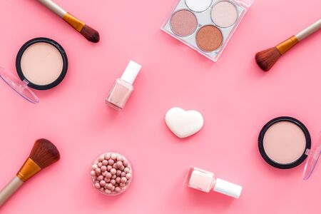 Makeup set with powder, rouge and brusheson pink background top view pattern