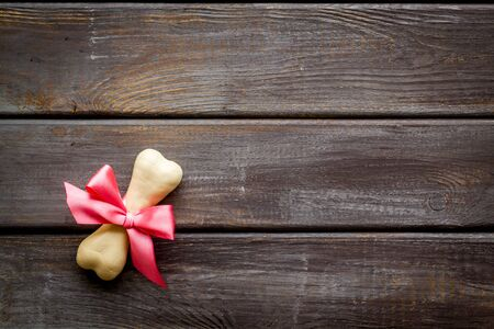 Small present for dogs. Chewing bones with bow on dark wooden background top view.
