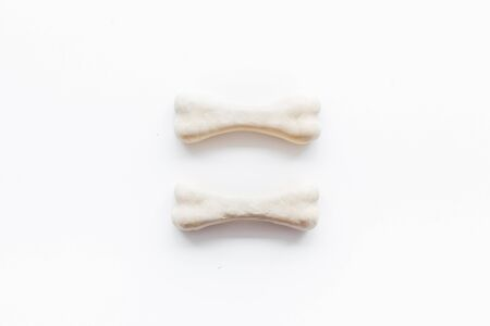 Food and toys for dogs. Chewing bones on white background top view.