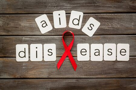 AIDS disease text near red ribbon on dark wooden background top view.
