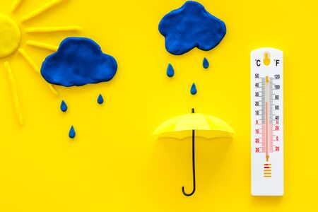 Rainy weather. Thermometer near clouds and drops on yellow background top view. Stock Photo