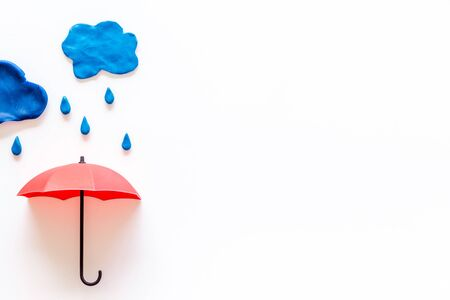Storm concept, bad weather. Clouds and umbrella on white background top view. Stock fotó