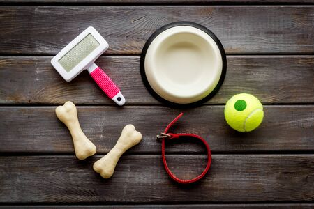 Set of treats and toys for pets with bones, collar and bowl on dark wooden background top view. Фото со стока - 131700634