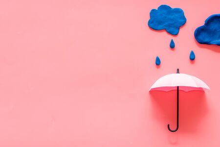 Storm concept, bad weather. Clouds and umbrella on pink background top view.