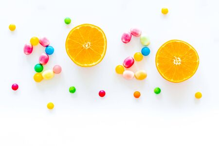 Sweet New Year design. 2020 laid out with candy and oranges on white background top view. 写真素材