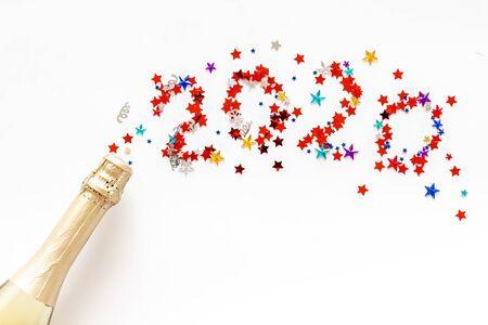 Świętuj Nowy Rok 2020. Data na konfetti w pobliżu butelki szampana na białym tle widok z góry.