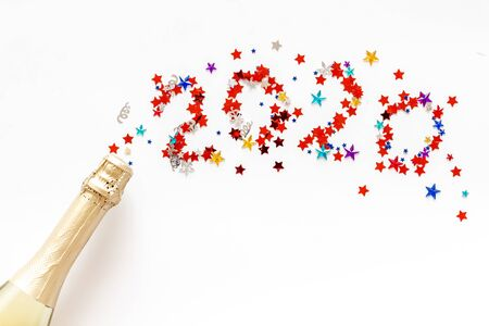 Celebrate New Year 2020. Date on confetti near champagne bottle on white background top view.