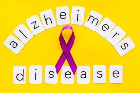 Alzheimers disease text near violet ribbon on yellow background top view.