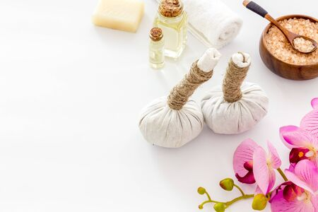 Massage thai herbal balls near spa accessories and orchids on white background. Stock Photo