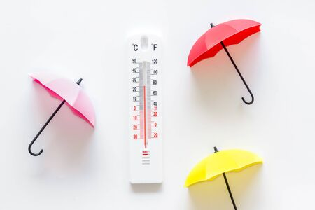 Rain concept. Weather thermometer near umbrella on white background top view.