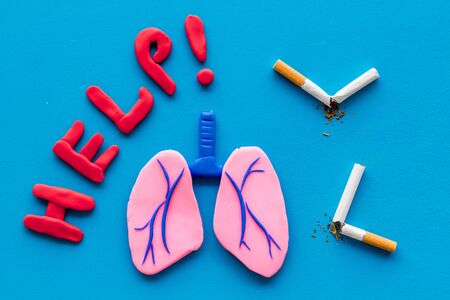 Harm of smoking and cancer. Word help, lungs and cigaretts on blue background top view.