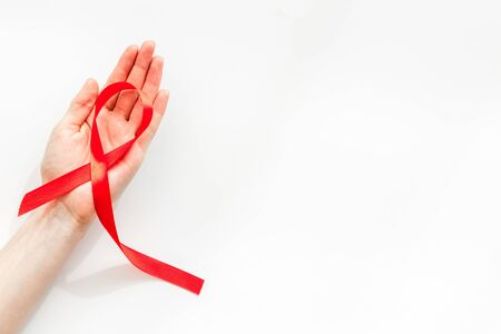 AIDS disease symbol. Red ribbon in hands on white background top view copy space 版權商用圖片