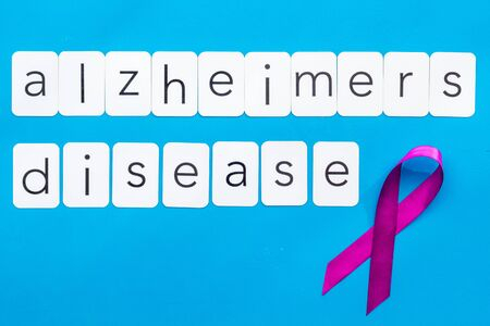 Alzheimers disease text near violet ribbon on blue background top view copy space Zdjęcie Seryjne