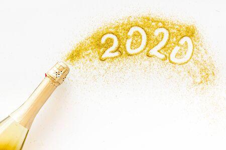 2020 Gelukkig Nieuwjaar-concept. Datum geschreven op gouden stof in de buurt van champagnefles op witte achtergrond bovenaanzicht. Stockfoto