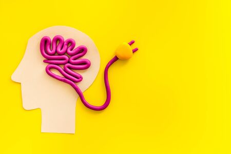 Brain charging and mental rest. Plug and cable leads to plastiline meanders on yellow background top view.