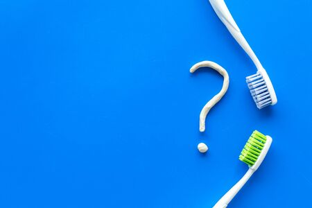 Dental problems concept. Question mark drawn with toothpaste near toothbrush on blue background top view