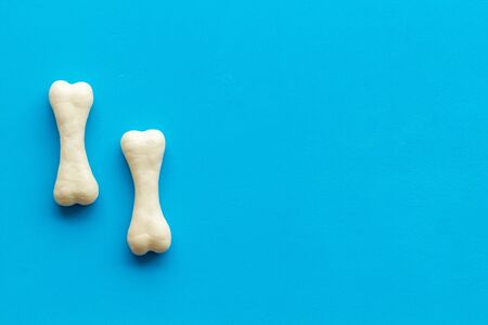 Food and toys for dogs. Chewing bones on blue background top view copy space