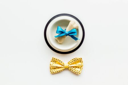 Dogs birthday concept. Chewing bones with bow and bow-tie on white background top view Фото со стока