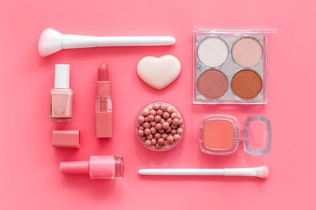 Makeup set with powder, rouge and brusheson pink background top view pattern.