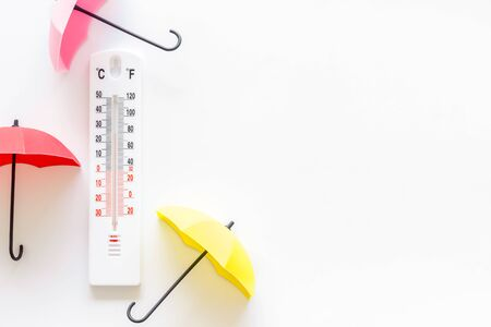 Concepto de lluvia. Termómetro meteorológico cerca del paraguas en el espacio de copia de vista superior de fondo blanco Foto de archivo