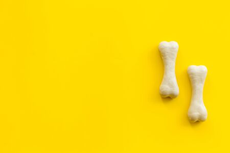 Treats for dogs. Chewing bones on yellow background top view copy space