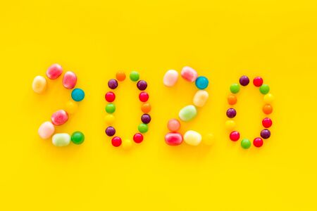Sweet New Year design. 2020 laid out with candy on yellow background top view copy space