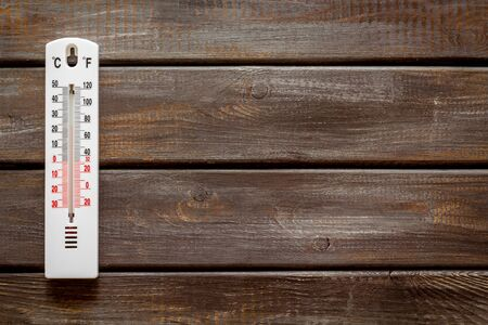 Weather thermometer on dark wooden background top view space for text
