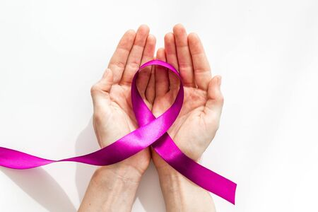 Lilac ribbon in hands is symbol of Alzheimers disease on white background top view Stock Photo