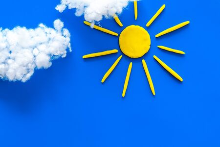 Cloudly weather concept. Sun and clouds on blue background top view copy space