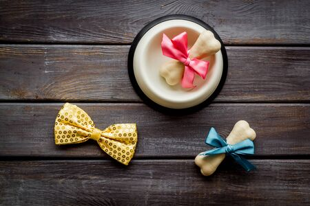 Dogs birthday concept. Chewing bones with bow and bow-tie on dark wooden background top view