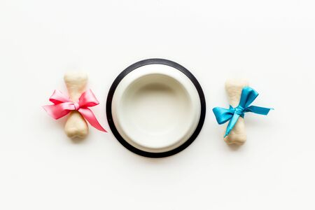 Dogs birthday concept. Chewing bones with bow in bowl on white background top view copy space mockup