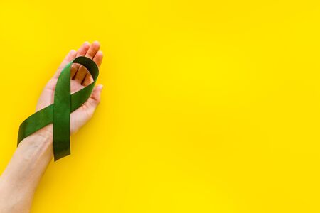 Jade ribbon in hands as symbol of disease control on yellow background top view space for text 写真素材